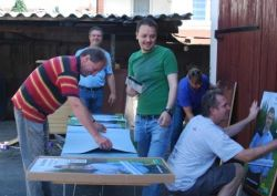 Mitglieder der FDP Maintal und Bürgermeisterkandidat Klaus Gerhard (im Hintergrund) beim Kleben der Wahlplakate